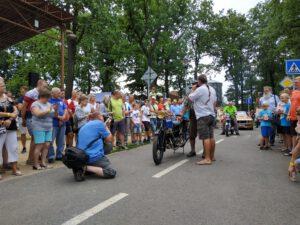 Grafika: Historická motorka stojí na dopravním hřišti, okolo ní stojí dav návštěvníků.