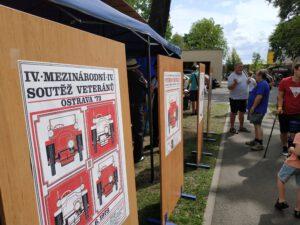 Grafika: Několik historických plakátů veteran klubu nalepených na dřevěných tabulích u stánku. Prohlíží si je několik lidí.