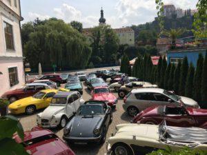 Grafika: Veterány členů VCCO zaparkované v historickém centru města.
