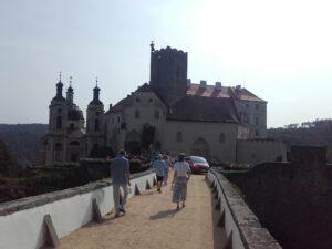 Grafika: Účastníci vyjížďky přecházejí přes most k hradu s kostelem.