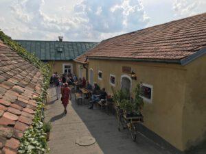 Grafika: Účastníci vyjížďky odpočívají u klasického jihomoravského stavení.