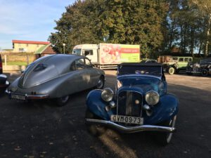 "Grafika: Aero a Tatra 600 zaparkované v Koblově u bistra ""U Januse""."